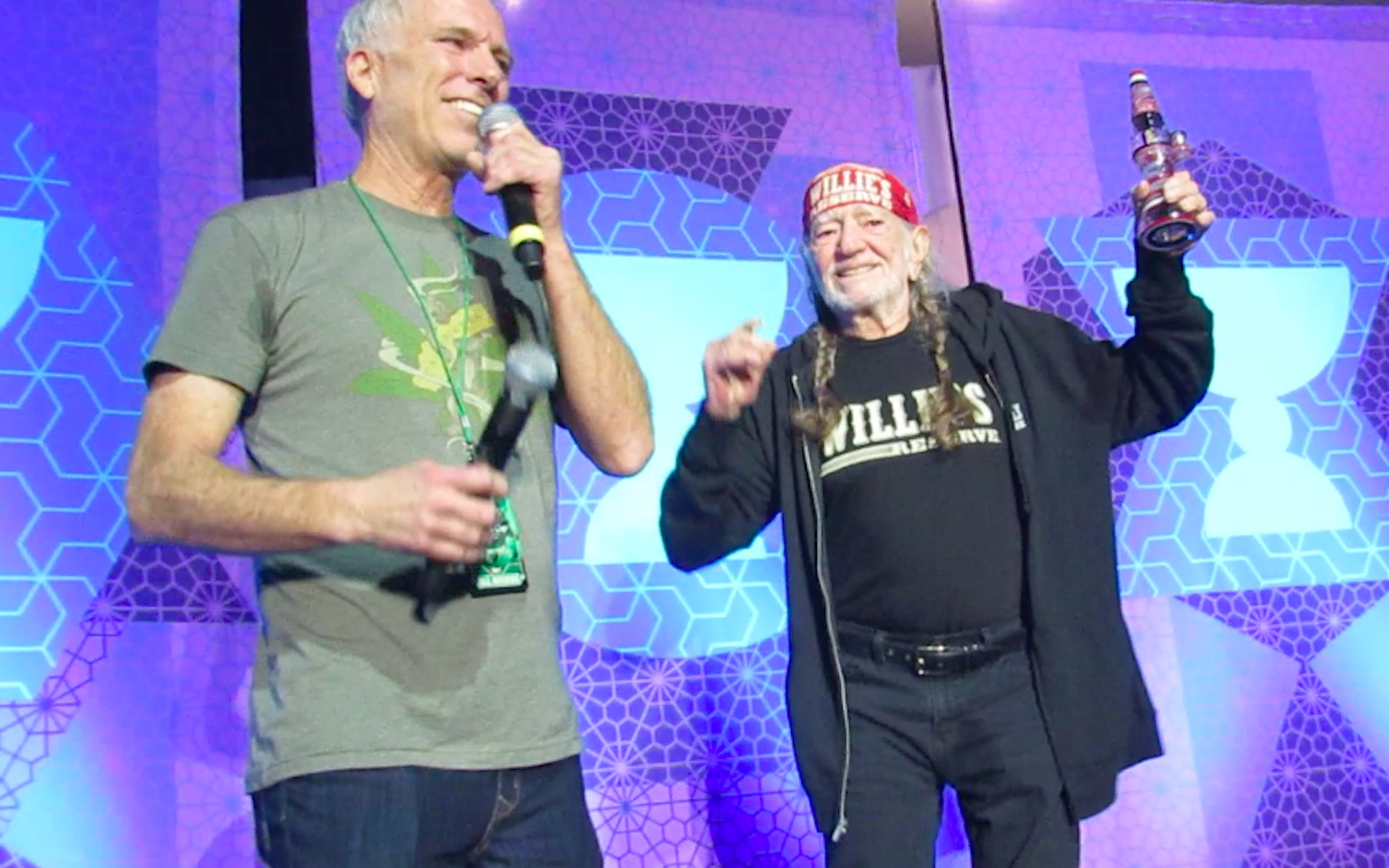 """Willie Nelson holds up his award, a custom Bluegrass """"lamp"""" bubbler. Cup organizer Tim Blake has been trying to book Willie for years. (David Downs/Leafly)"""
